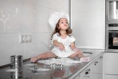 La petite fille fait la pâte sur la cuisine avec la goupille photographie stock libre de droits
