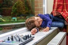 La petite fille a fatigué après jeu d'échecs Photo stock