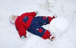 La petite fille fatiguée se trouve sur la neige près de la grande boule de neige Image libre de droits