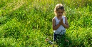 La petite fille a fermé ses yeux priant au coucher du soleil Les mains se sont pliées dans le concept de prière pour la foi, la s photos libres de droits