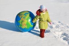 La petite fille frotte le grand globe gonflable Images libres de droits