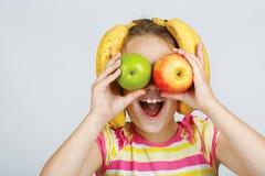 La petite fille gaie avec les pommes, le citron et la banane pose le positiv images libres de droits