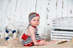 La petite fille gaie dans un style marin s'assied sur le sable Image libre de droits