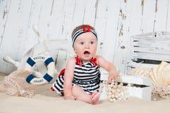 La petite fille gaie dans un style marin s'assied sur le sable Images stock
