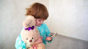 La petite fille gaie fait des visages sur le ` s de mère téléphoner banque de vidéos