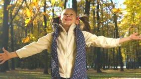 La petite fille gaie jette des feuilles d'automne devant la caméra dans le mouvement lent banque de vidéos
