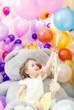 La petite fille gaie saisit le groupe de ballons Photographie stock