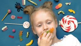 La petite fille gaie se trouve sur un fond bleu avec des bonbons Verticale de plan rapproch? banque de vidéos