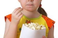 La petite fille garde le module avec le maïs éclaté Image libre de droits