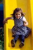 La petite fille glisse dans le terrain de jeu Photo libre de droits