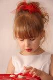 La petite fille goûte le petit gâteau Photo stock