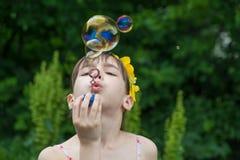 La petite fille gonfle des bulles de savon image libre de droits