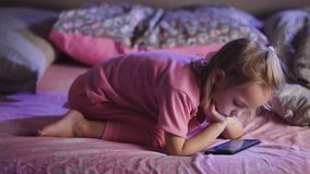 La petite fille habillée dans des pyjamas roses avec le téléphone portable dans des ses mains se situe dans le lit et les bandes  banque de vidéos