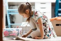 La petite fille habillée dans la robe et les collants dessine dans l'album se reposant sur le plancher dans la chambre photos libres de droits