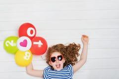 La petite fille heureuse avec des lunettes de soleil, tenant l'arc-en-ciel monte en ballon Images stock