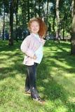 La petite fille heureuse avec les cheveux rouges dans le diadème pose Photos stock