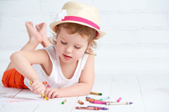 La petite fille heureuse d'artiste dans un chapeau dessine le crayon Photographie stock