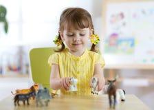 La petite fille heureuse d'enfant en bas âge joue le zoo à la maison ou le service de garderie images libres de droits