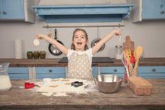 La petite fille heureuse dans la cuisine fait différentes formes des biscuits hors de la pâte, aidant sa maman Petite aide images stock