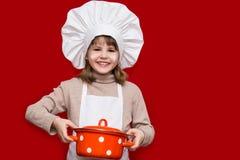 La petite fille heureuse dans l'uniforme de chef juge la casserole d'isolement sur le rouge Chef d'enfant photos libres de droits