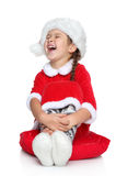 La petite fille heureuse dans le chapeau de Santa rit sur un blanc Images stock