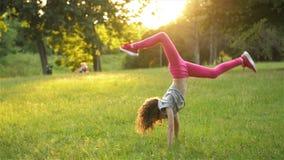 La petite fille heureuse dans la robe saute sur le pré de parc et fait la roue acrobatique Activit?s en plein air d'?t? Mouvement banque de vidéos