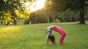 La petite fille heureuse dans la robe saute sur le pré de parc et fait la roue acrobatique Activit?s en plein air d'?t? Mouvement clips vidéos