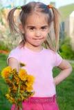 La petite fille heureuse donnant fleurit Images stock