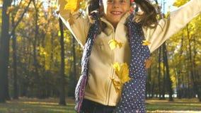 La petite fille heureuse en parc jette des feuilles d'automne vers la caméra dans le mouvement lent clips vidéos