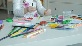 La petite fille heureuse joue avec de la pâte à modeler, sculpte une figure, sur le bureau sont des figures et des crayons coloré banque de vidéos