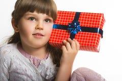 La petite fille heureuse a mis le boîte-cadeau à l'oreille d'isolement sur le fond blanc Image stock