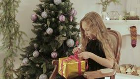 La petite fille heureuse ouvre un cadeau magique de Noël par la cheminée pendant la nouvelle année banque de vidéos