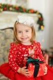 La petite fille heureuse portant la robe rouge, gardant le cadeau et s'asseyant sur le sofa près a décoré la cheminée images libres de droits