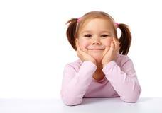 La petite fille heureuse s'assied à une table et à un sourire Photographie stock libre de droits