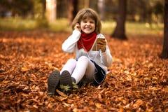 La petite fille heureuse s'assied sur les feuilles jaunes et écoute la musique en automne photos libres de droits