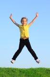La petite fille heureuse saute à l'herbe photos libres de droits