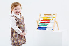 La petite fille heureuse se tient près de l'abaque coloré Photos stock
