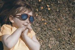 La petite fille heureuse se trouve sur l'herbe et regarde le ciel Dans des lunettes de soleil nuages reflétés photographie stock libre de droits