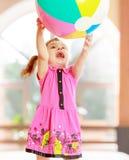 La petite fille jette la boule photo stock