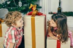 La petite fille jette un coup d'oeil par derrière le grand boîte-cadeau de Noël et regarde le garçon de sourire Images stock
