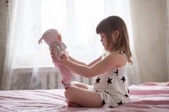 La petite fille jouant le docteur sur le lit, fille traite la poupée, le r Photographie stock