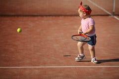 La petite fille joue au tennis Image stock
