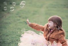 La petite fille joue avec des bulles Photographie stock libre de droits