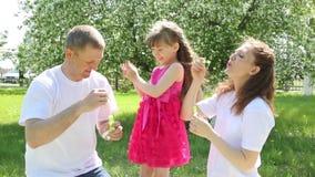 La petite fille joue avec des bulles de savon banque de vidéos