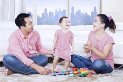 La petite fille joue avec le parent sur le tapis Images stock