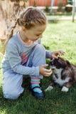 La petite fille joue avec un chien un chien comme cadeau aux enfants sourire du ` s d'enfants sur la nature Images stock