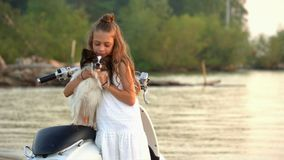La petite fille joue avec un petit chien sur la plage La belle fille a un repos à la mer avec un petit chien banque de vidéos