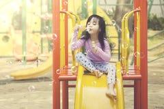 La petite fille joue des bulles de savon au terrain de jeu Photos stock