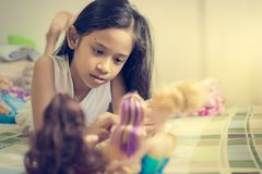 La petite fille joue des poupées sur le lit photos libres de droits