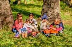 La petite fille joue la guitare à un groupe des amis et d'un costaud Photo stock
